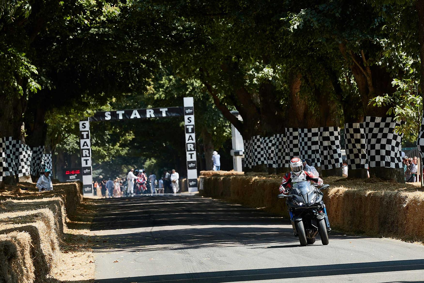 Alex Lowes rides a Yamaha Niken up the start of the famous Goodwood hill-climb