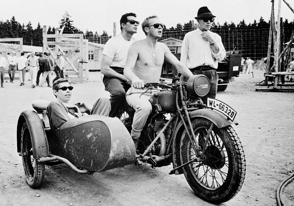 Steve McQueen riding a motorbike and sidecar