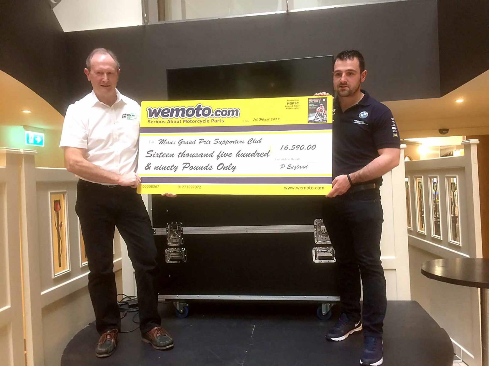 Michael Dunlop helps present a cheque