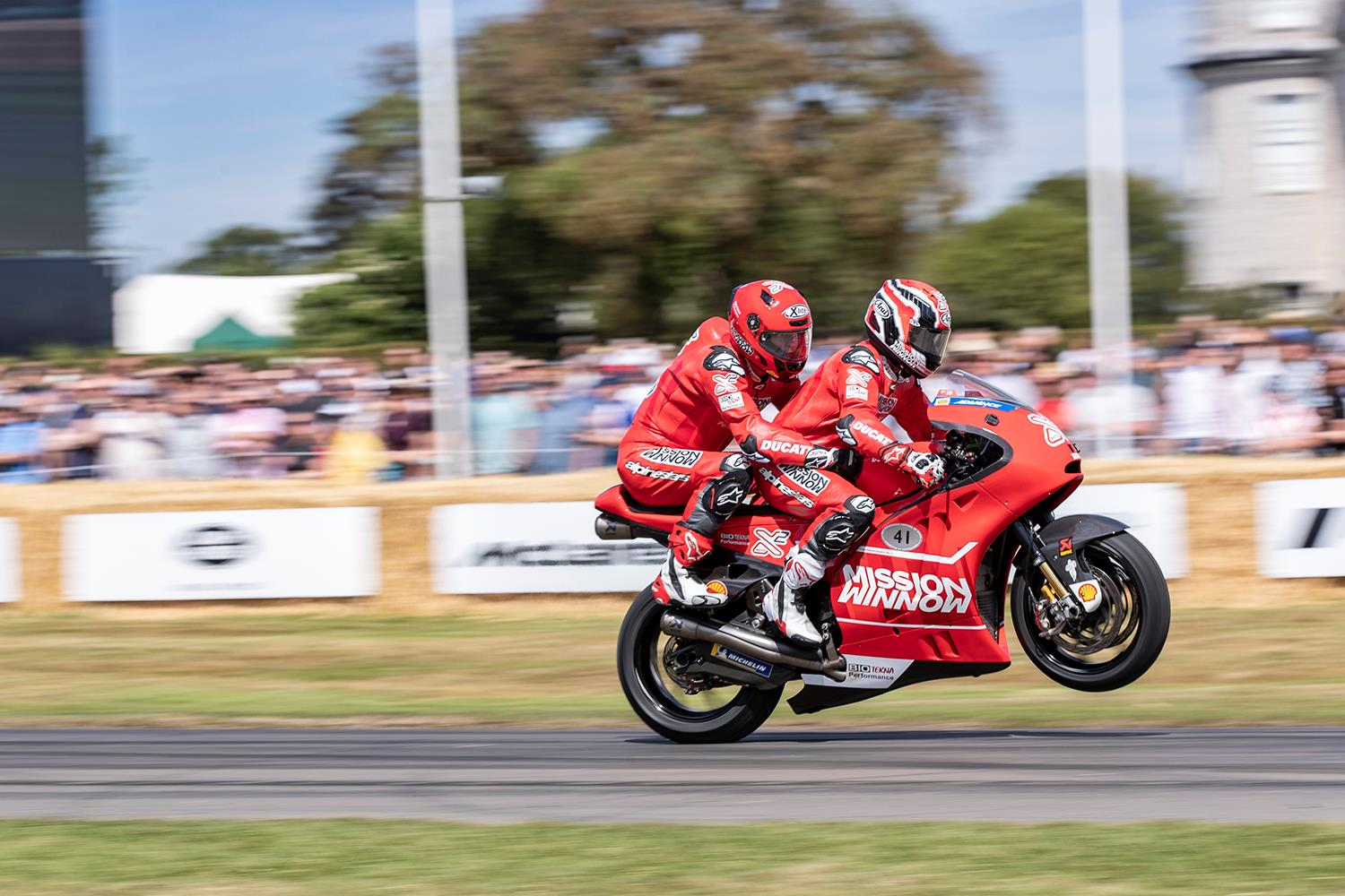 Randy Mamola gives a passenger ride at Goodwood