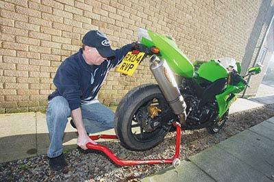 1 hook up the hose to the pressure washer or spray nozzle and then place the bike on its sidestand or preferably on a paddock stand to get access to the